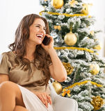 Happy woman talking cell phone while sitting near christmas tree Royalty Free Stock Photos