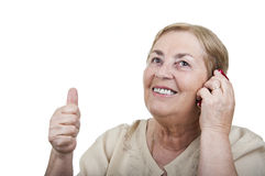 Happy woman talking at cellphone with thumb up Stock Image