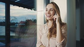 Happy woman talking mobile in house. Portrait of smiling woman speaking phone. stock video footage