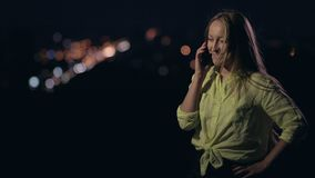 Happy woman talking on mobile phone at night stock video