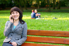 Happy woman talking on mobile phone in park Royalty Free Stock Photos