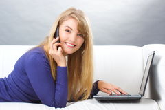 Happy woman talking on mobile phone and using laptop lying on sofa, modern technology Stock Photos