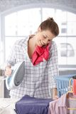 Happy woman talking on phone while ironing Royalty Free Stock Photo