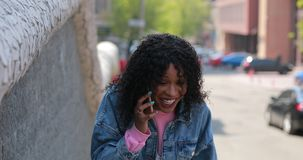 Happy woman talking by phone with laugh in city stock video footage