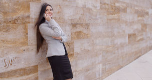 Happy woman talking on phone and leaning on wall Royalty Free Stock Photos