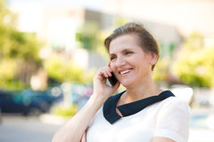 Happy Woman Talking on a Phone. Portrait Beautiful mature woman or businesswoman in her forties talking on a cell phone, having pleasant conversation, receiving Royalty Free Stock Images