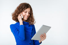 Happy woman talking on the phone and using tablet computer Royalty Free Stock Photos