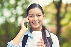Happy woman talking on smart phone. Portrait young businesswoman professional walking outdoors talking on cell smart phone drinking coffee from disposable paper Stock Photography