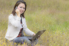Happy woman talking on smartphone  and working on laptop Royalty Free Stock Photo