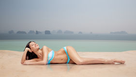 Happy woman tanning in bikini over swimming pool Royalty Free Stock Image