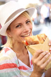 Happy woman tasting Focaccia sandwich Stock Images
