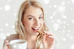Happy woman with tea eating cookie in winter. Morning, breakfast, food and people concept - happy young woman with cup of tea eating cookie over snow Stock Images