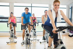 Happy woman teaches spinning class to four people Stock Photo