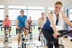 Happy woman teaches spinning class to four people. Portrait of a happy women teaches spinning class to four people at gym Stock Photos
