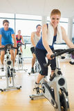 Happy woman teaches spinning class to four people Royalty Free Stock Image