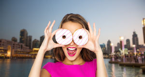 Happy woman or teen girl looking through donuts Stock Images