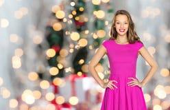 Happy woman or teen girl over christmas lights Stock Photo