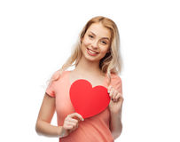 Happy woman or teen girl with red heart shape. Love, romance, charity, valentines day and people concept - smiling young woman or teenage girl with blank red Royalty Free Stock Photography