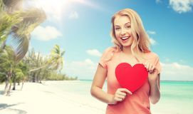 Happy woman or teen girl with red heart shape. Love, travel, tourism, valentines day and people concept - smiling young woman or teenage girl with blank red Stock Photos