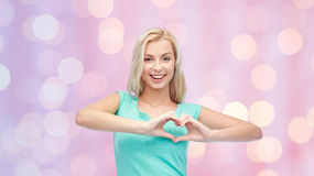 Happy woman or teen girl showing heart shape sigh Stock Photo