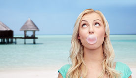 Happy woman or teenage girl chewing gum on beach Stock Images