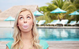 Happy woman or teenage girl chewing gum on beach Stock Photography