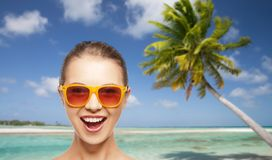 Happy woman or teenage girl in sunglasses on beach stock photos