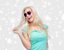 Happy woman or teenager in heart shaped sunglasses Royalty Free Stock Images