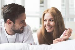 Happy woman telling man about her expectant position. Portrait of excited loving couple expressing happiness while looking at pregnancy test. They are lying on Royalty Free Stock Photography