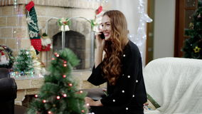 Happy woman telling by a phone at christmas time. Beautiful Woman telling about gifts to christmas. Woman calling to friend and talking stock video footage