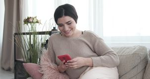 Happy woman using mobile phone at home. Happy woman text messaging on mobile phone while relaxing on sofa at home stock video footage
