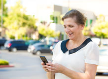 Happy woman texting on her smart phone. Closeup portrait middle aged, happy, smiling woman texting on her smart phone, isolated outdoor parking lot background Royalty Free Stock Photos