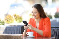 Happy woman is texting on smart phone in a coffee shop stock image