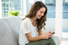 Happy woman texting on sofa Royalty Free Stock Photos