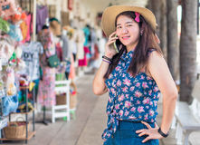 Happy woman at Thailand shopping market is using her mobile phon Royalty Free Stock Image