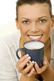 Happy woman thinking holding a cup of tea stock image