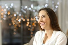 Happy woman thinking looking at side in the night. Sitting on a couch in the living room at home stock image