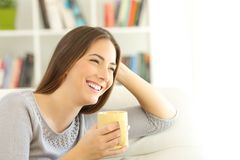 Happy woman thinking looking at side at home. Happy woman thinking looking at side sitting on a couch in the living room at home with white isolated space at Stock Photography