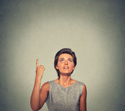 Happy woman thinking looking up pointing with finger at blank copy space Stock Photos