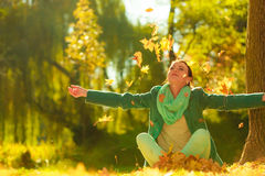 Happy woman throwing autumn leaves in park Royalty Free Stock Photos