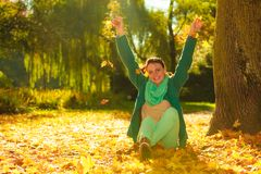 Happy woman throwing autumn leaves in park Stock Photo
