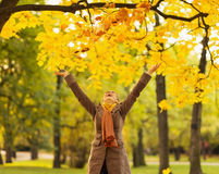 Happy woman throwing fallen leaves Stock Photography