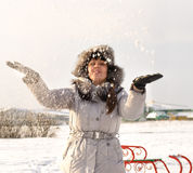 Happy woman throwing snow into the air Royalty Free Stock Images