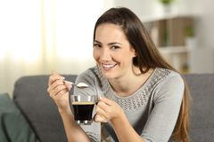 Happy woman throwing sugar into coffee looking at you. Sitting on a couch in the living room at home Stock Image