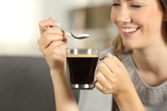 Happy woman throwing sugar into coffee with a spoon. Close up of a happy woman hand throwing sugar into coffee with a spoon sitting on a couch in the living room Stock Image