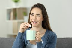 Happy woman throwing sugar into mug looking at you. Sitting on a couch in the living room at home stock image