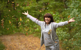 Happy woman throws up autumn leaves Royalty Free Stock Photo