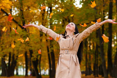 Happy woman throws up autumn leaves up Royalty Free Stock Photos
