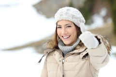 Happy woman with thumb up keeping warm in winter. In a snowy mountain Royalty Free Stock Photography