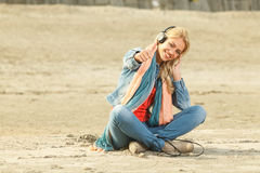 Happy woman with thumbs up listening to music with headphones Royalty Free Stock Images